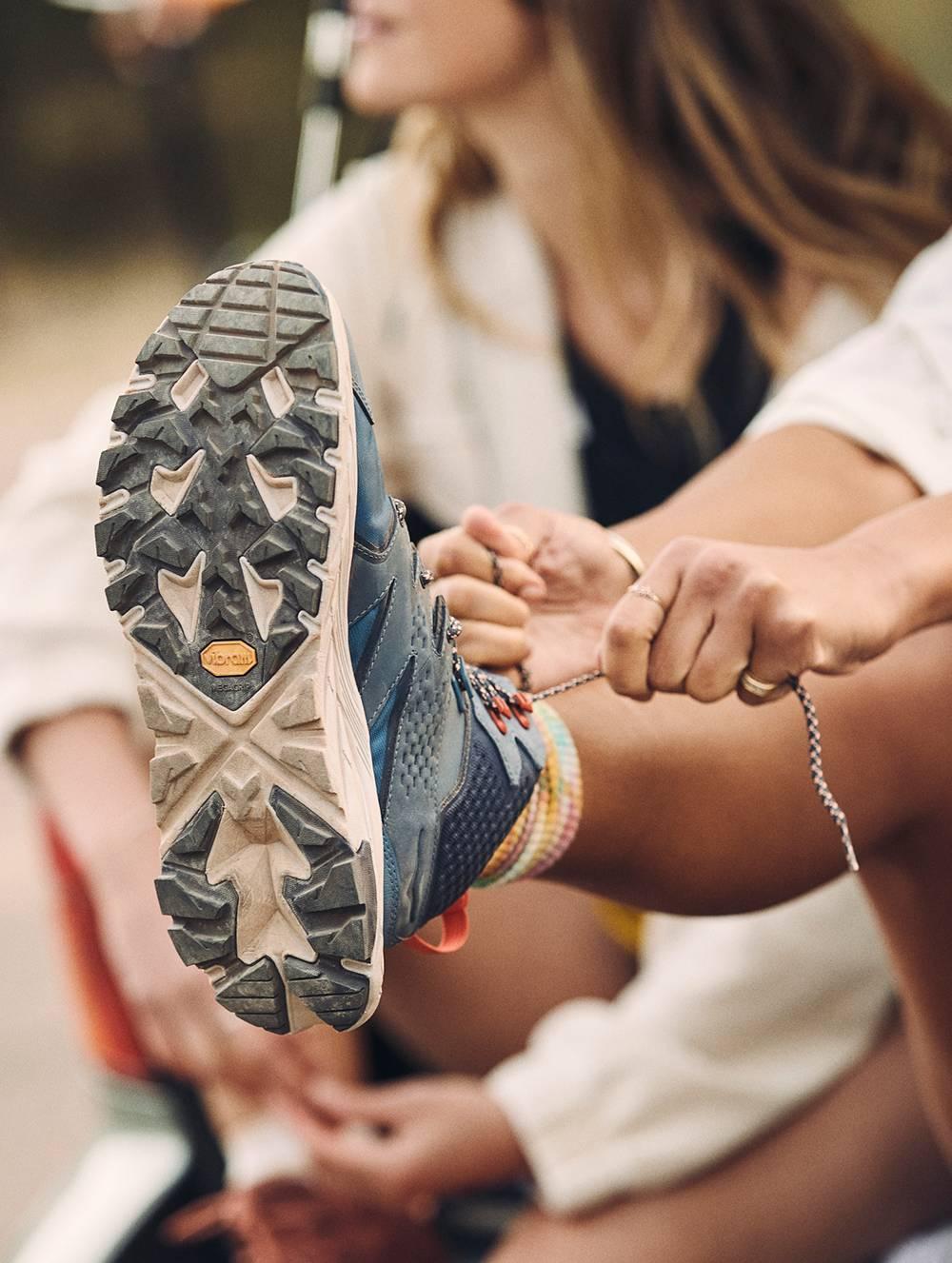 Femme montrant la semelle de la chaussure ANACAPA MID GTX