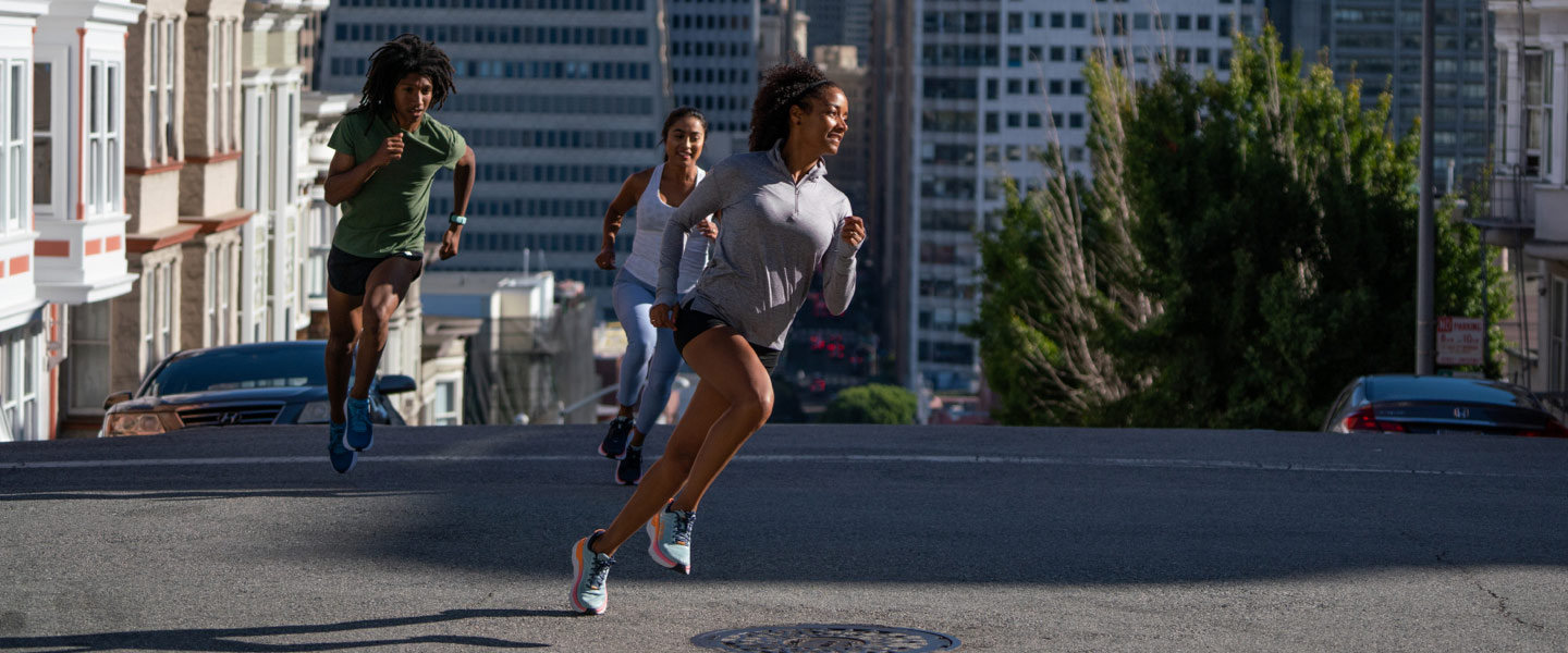 Three people running on a street in a city