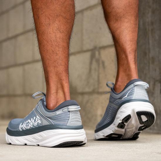 Close up of someone standing, wearing HOKA Bondi 7 shoes