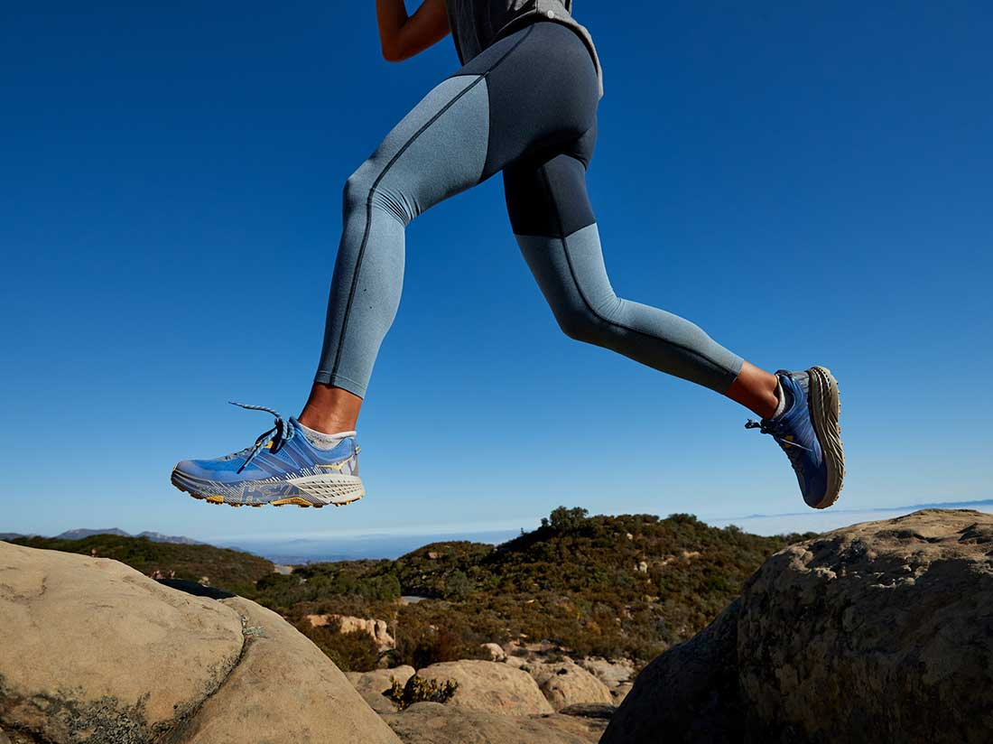 A woman jumping over rocks