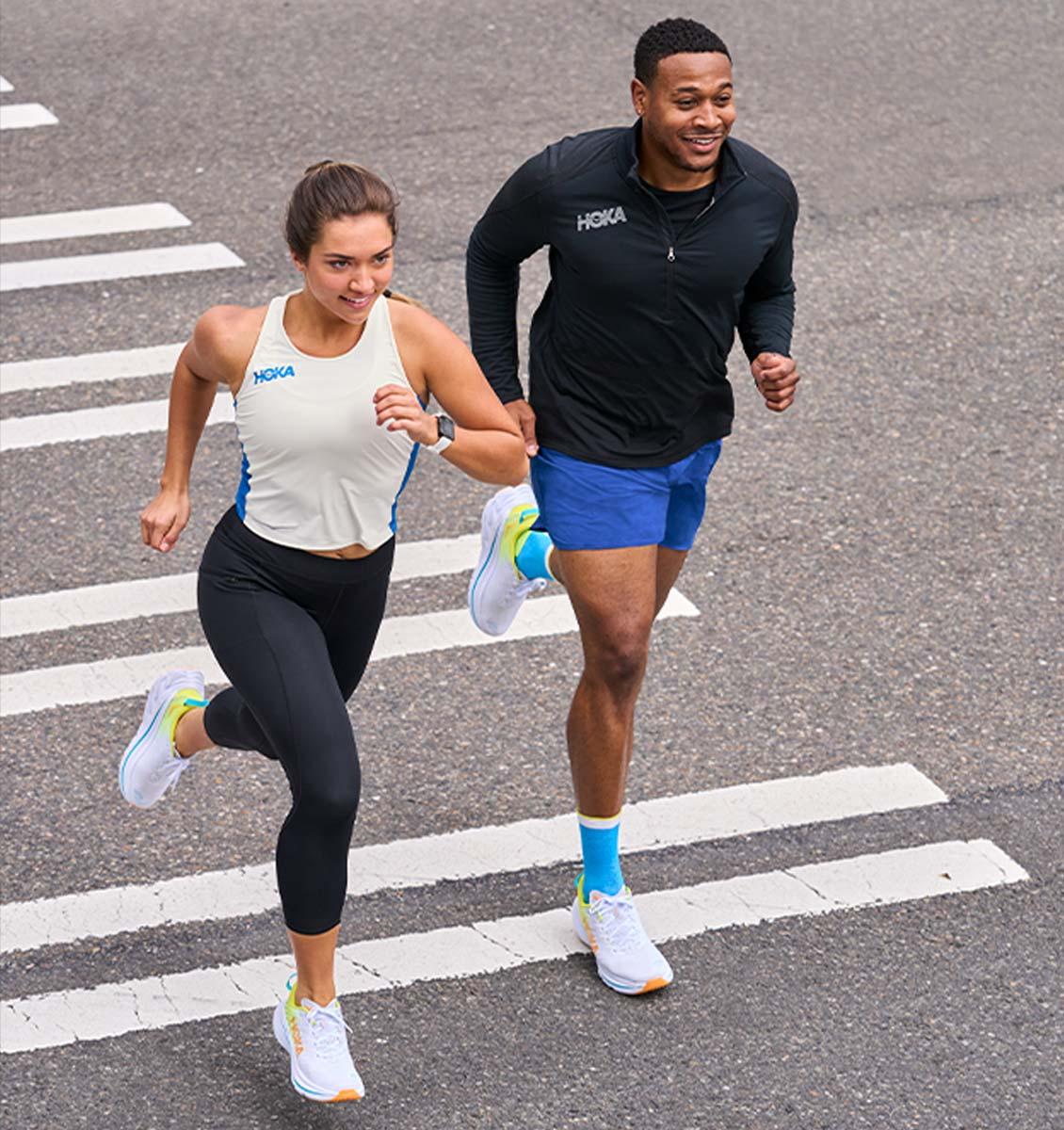 Runnning couple wearing Bondi X shoes crossing the street