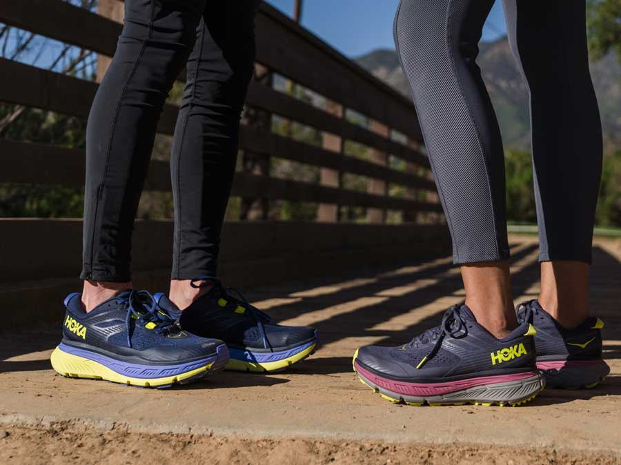 A close up for two people wearing HOKA shoes