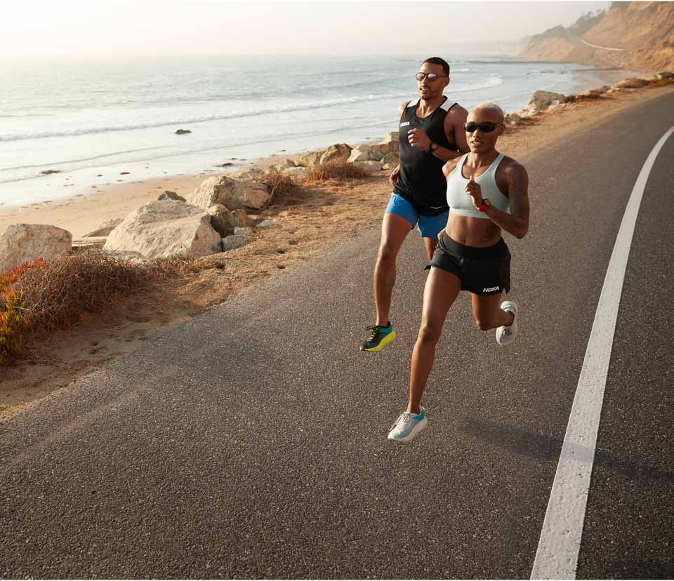 Two people running next to the beach
