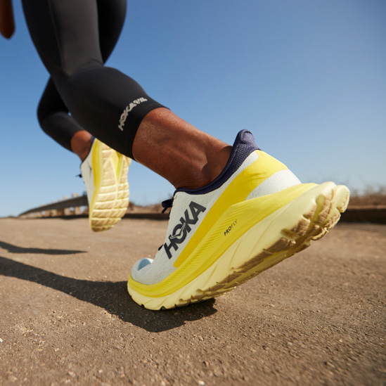 Close up of someone standing, putting on HOKA Clifton 7 shoes