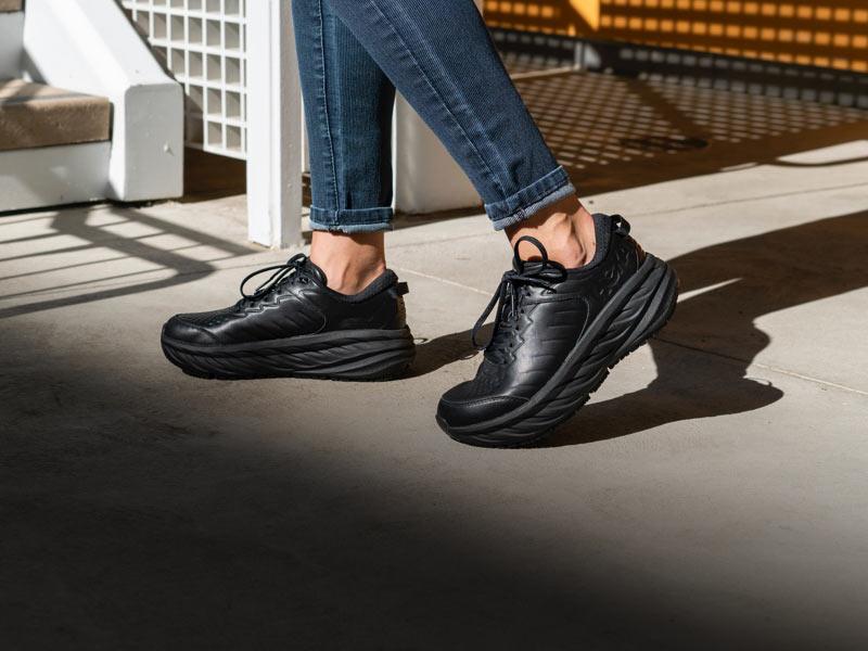 Woman walking in city, wearing HOKA shoes.