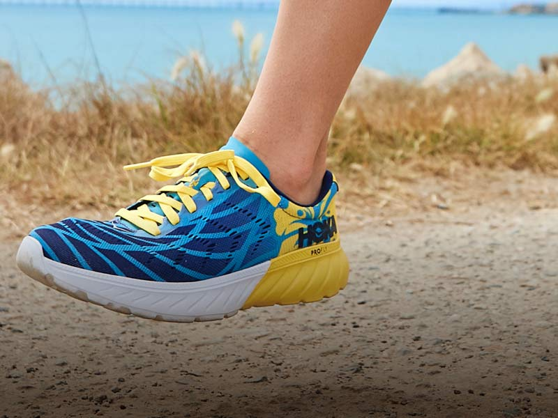 Woman running on path near ocean, wearing HOKA blue and yellow shoes.