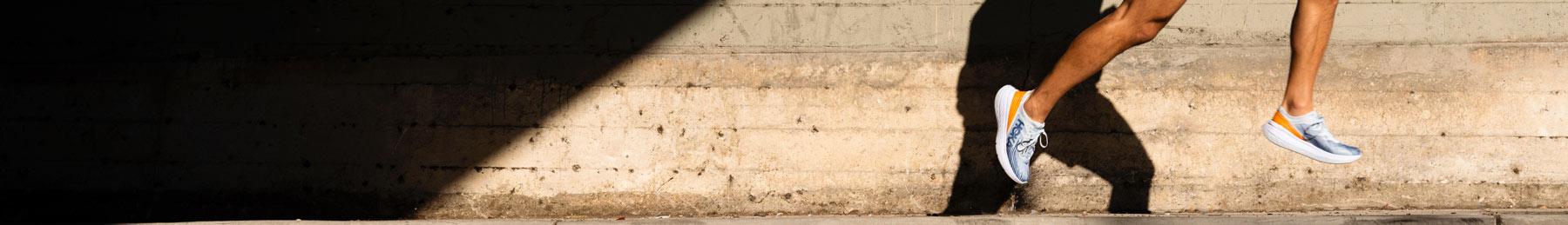 Man running down road by concrete wall wearing HOKA shoes.