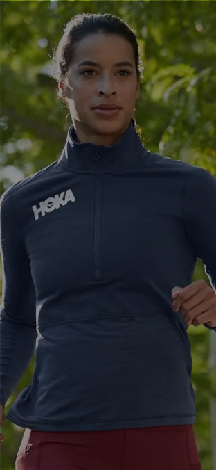 A man woman in the forest in a HOKA jacket