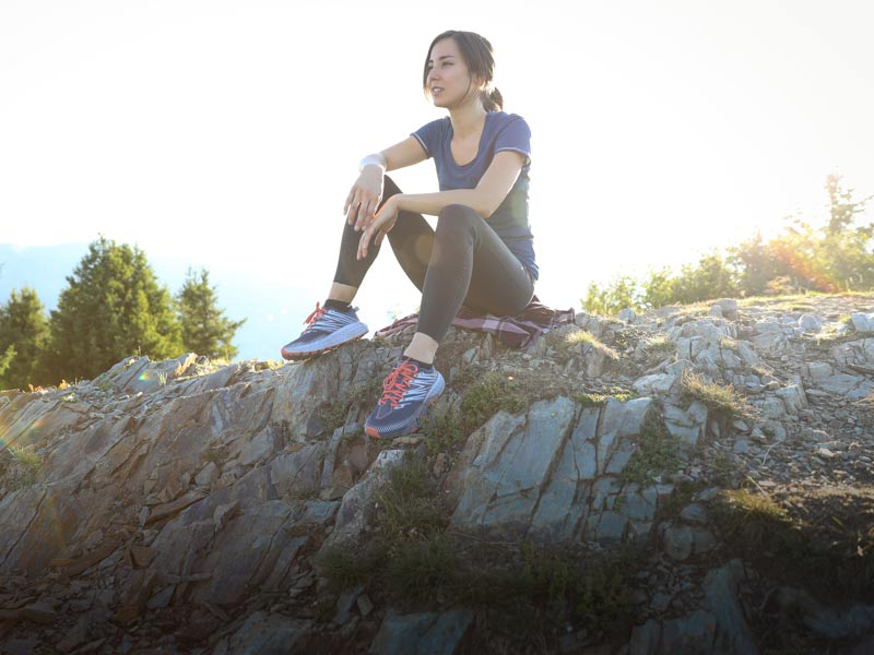 Woman sitting on rock ledge, wearing HOKA shoes.