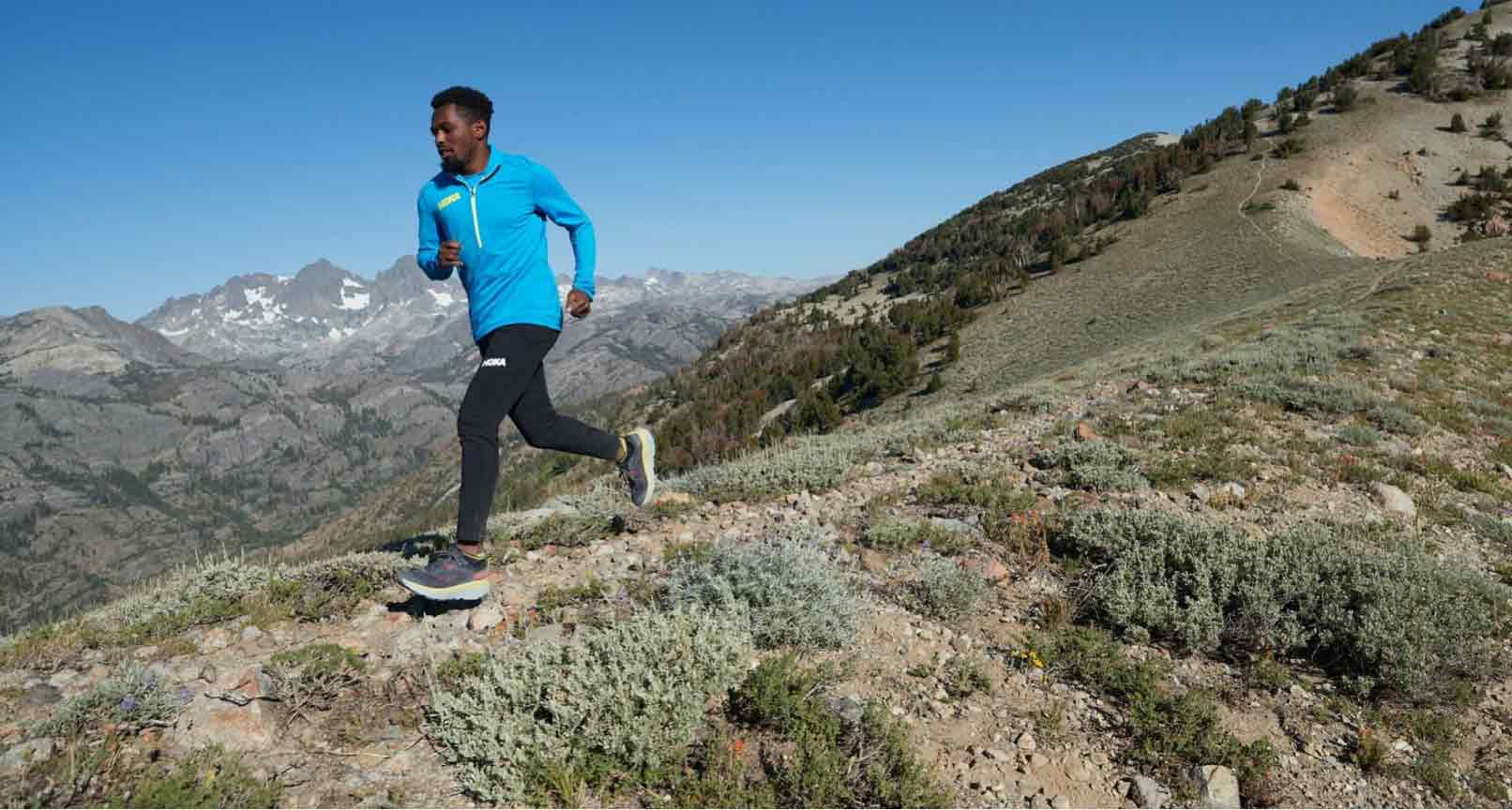 A man running on a trail with a mountain in the background