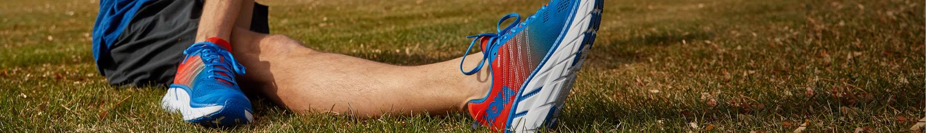Man streching in grass wearing HOKA shoes.