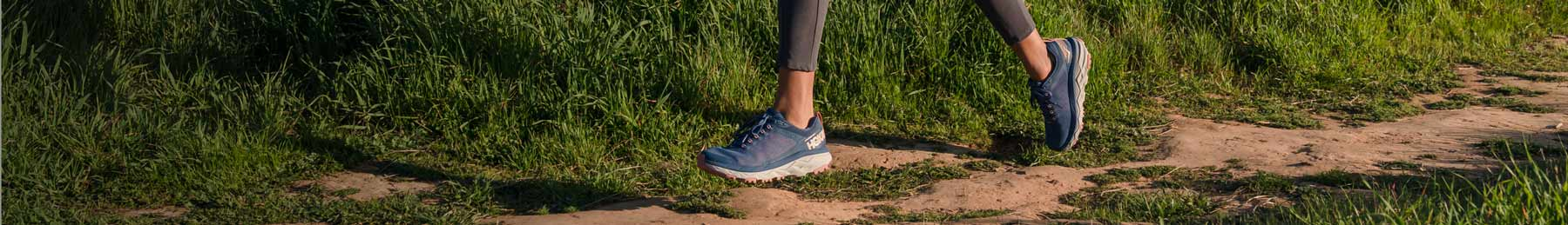 Woman running down forest trail, wearing HOKA shoes.