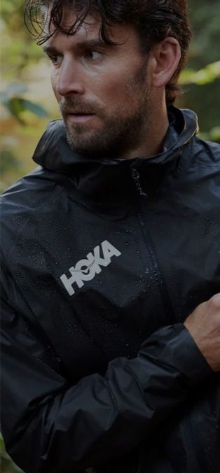 A man standing in the forest in a HOKA jacket