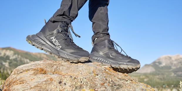 Man hiking on a rock in Hoka running shoes