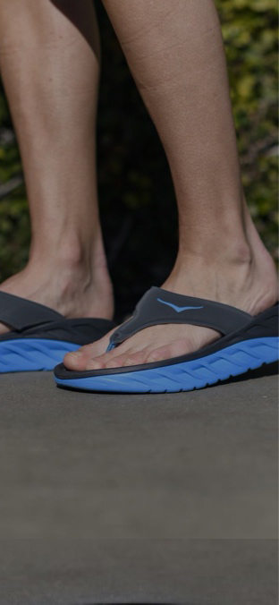 A woman standing in HOKA sandals