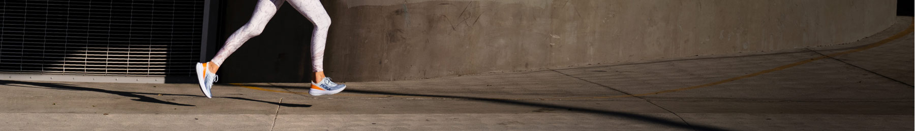 Woman running down road by concrete wall wearing HOKA shoes.
