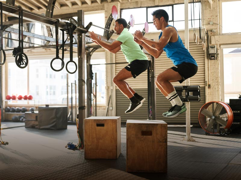 Men jumping onto wodden box in athletic apparel