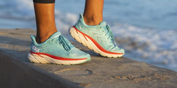 Woman standing near the sea in Hoka running shoes