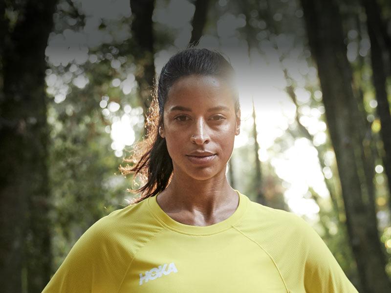 Woman in forest, wearing HOKA apparel.