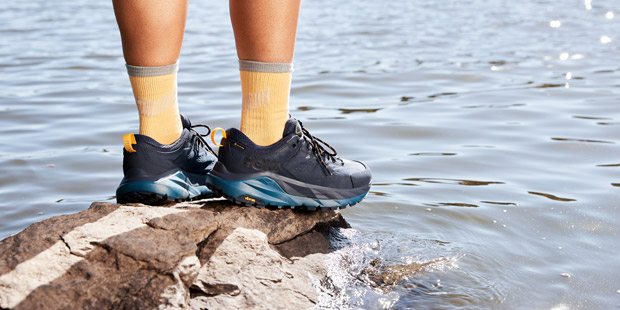 Woman standing on a rock above water in HOKA hiking shoes