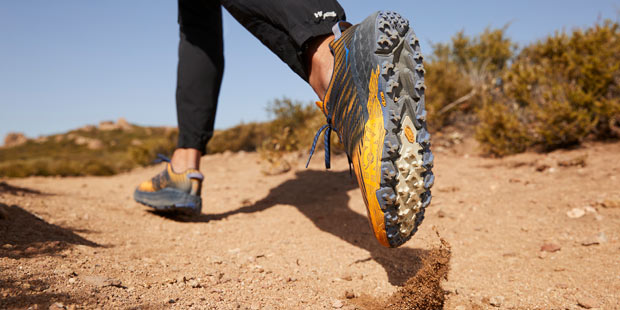 Man walking on a trail in Hoka running shoes