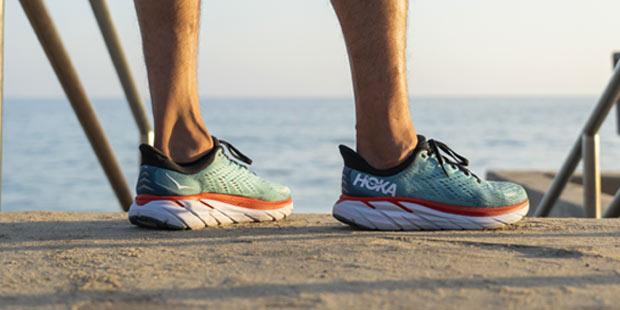 Man standing near the sea in Hoka running shoes