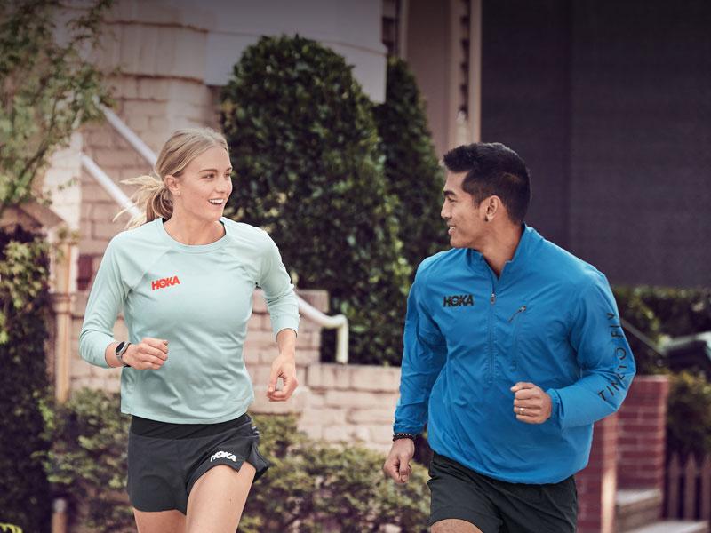 Woman and mann running through neighborhood in HOKA athletic apparel