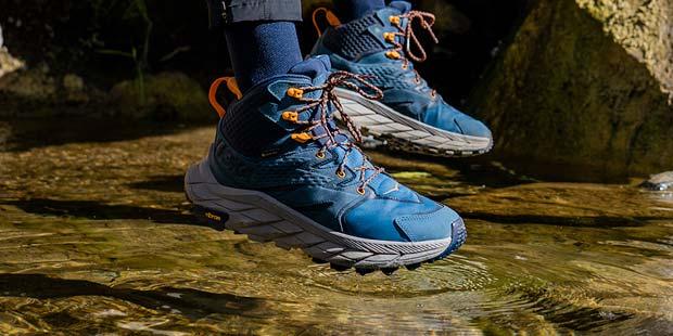 Man walking the through a river in Hoka hiking shoes