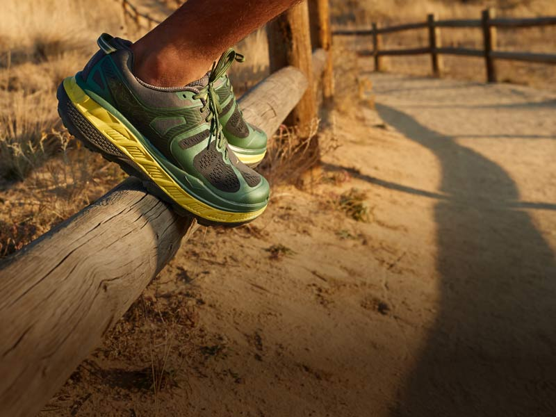 Person standing on wooden fence wearing HOKA shoes.