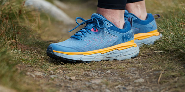 Woman standing on a trail in Hoka running shoes