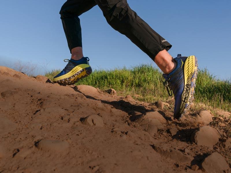Man running up dirt trail wearing HOKA shoes.