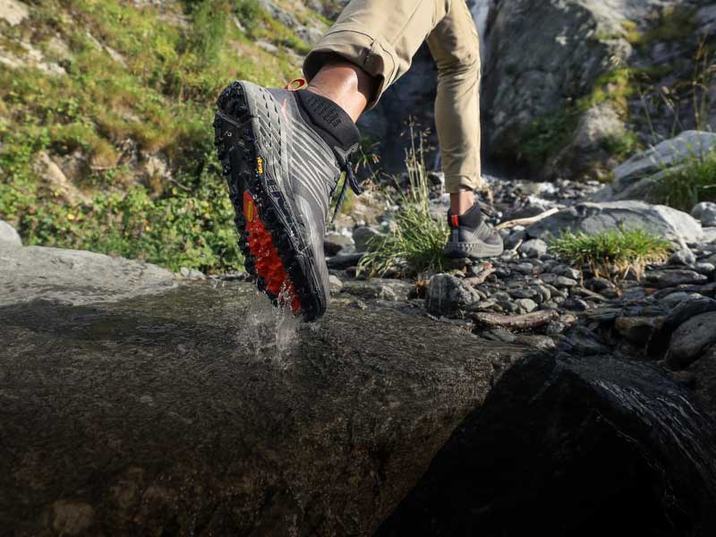 Man running over rocks, wearing HOKA shoes.